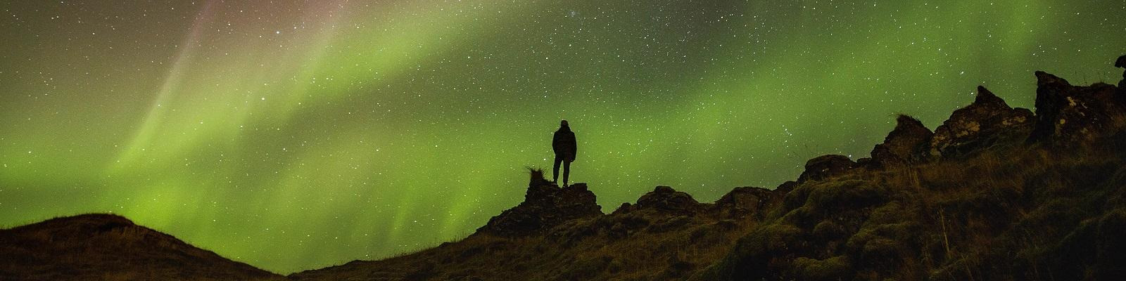 Figure silhouetted by the northern lights in Iceland