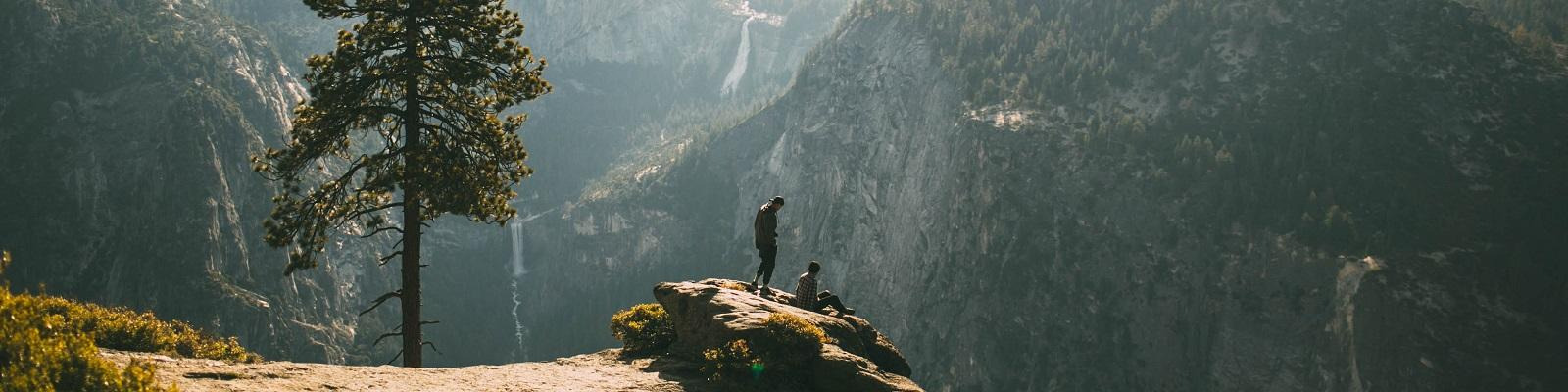 People on a rock overlooking Half Dome, Yosemite National Park, California