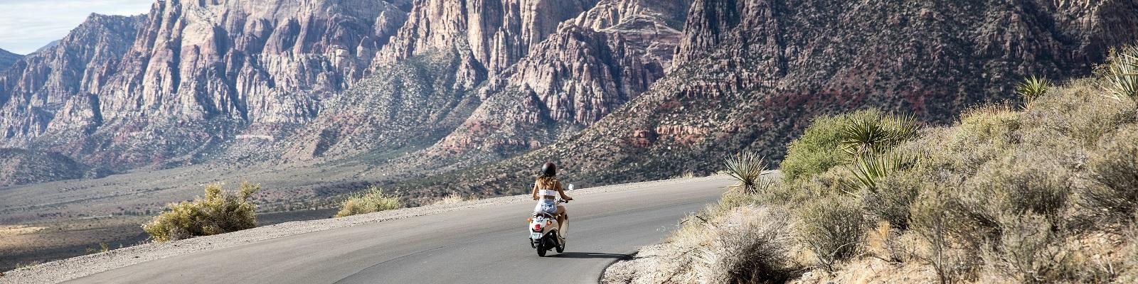 A person riding a scooter through Red Rock Canyon, Nevada