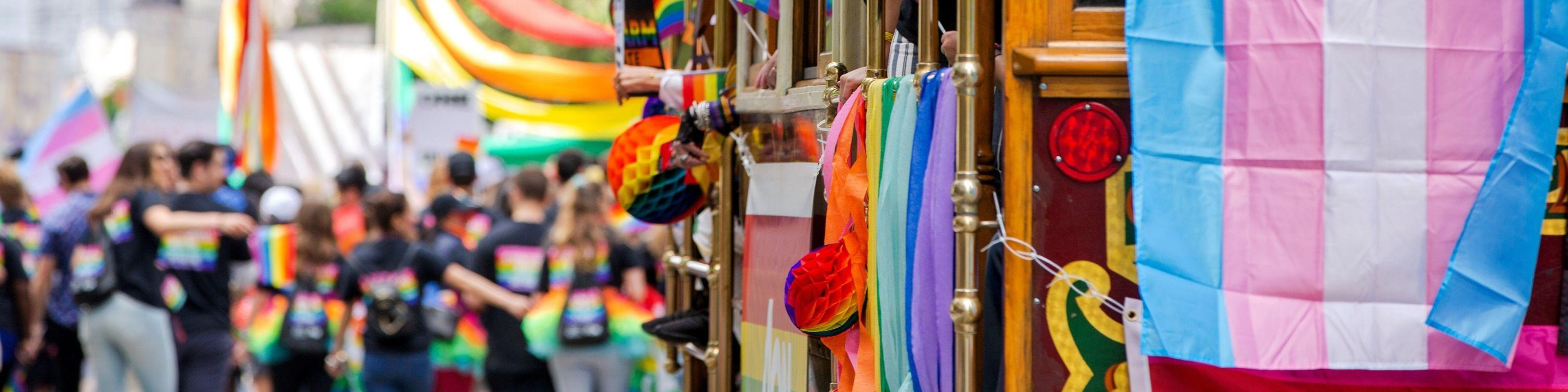 People walk alongside a tram draped in rainbow and Trans flags at the San Francisco Pride parade.