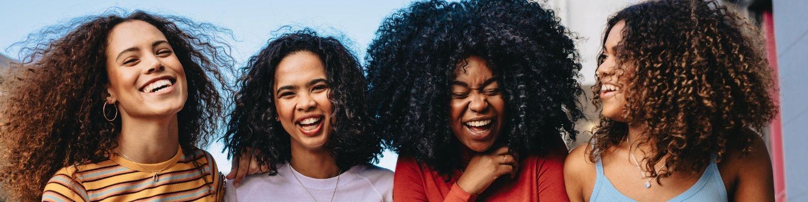 Four Black women walk down the street laughing during a girls' weekend.