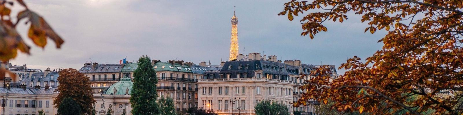 A shot of Paris, France from across the river with the Eiffel Tower twinkling in the distance.
