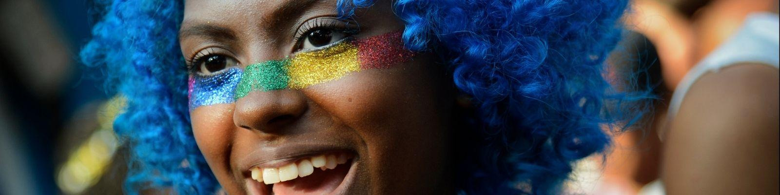 Person with rainbow face paint celebrates Pride in Brazil.