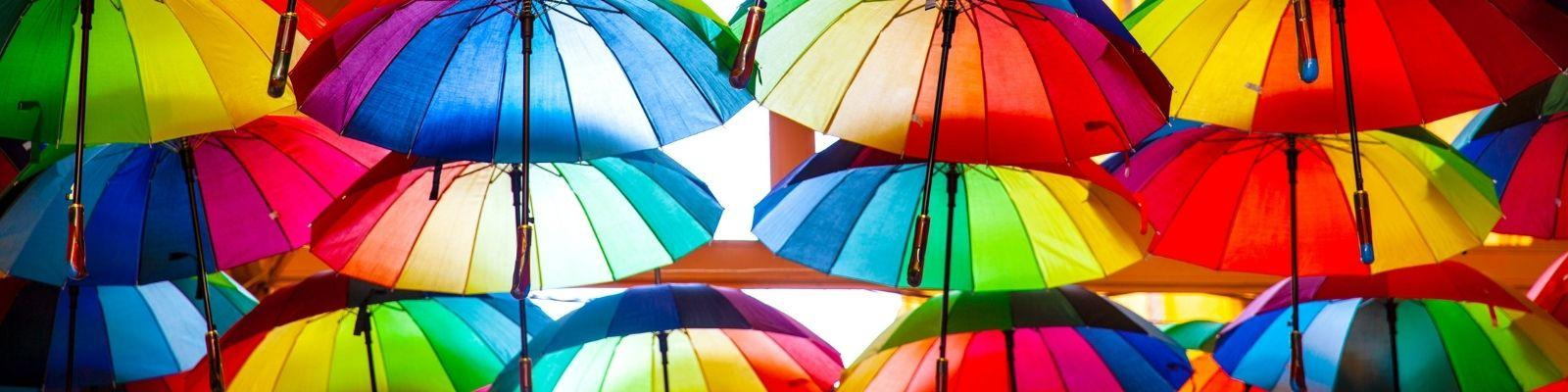 Rainbow Pride umbrellas hang suspended from the roof.