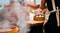 Chefs preparing dumplings alongside stacked dim sum steamers
