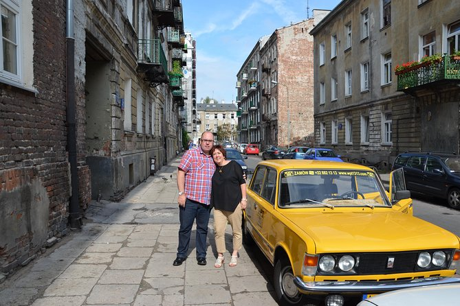 Couple standing next to a Yellow Fiat in Warsaw: Jewish Tour in Warsaw by Retro Fiat