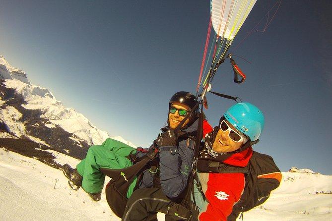 Tandem paragliding over ski slopes