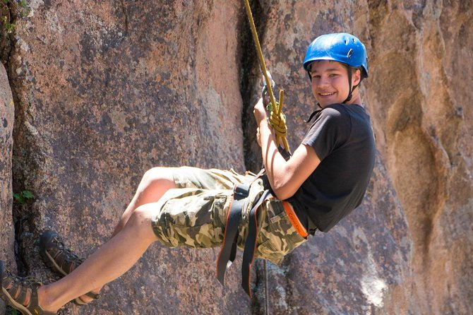 Rappelling down a rock-face.
