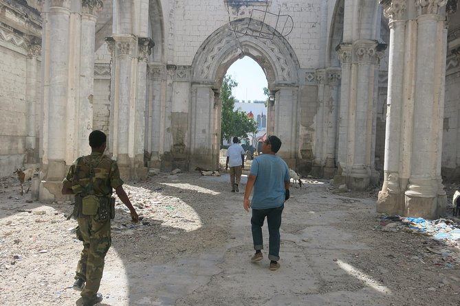 Traveler escorted by armed guards, wandering in the ruin of the Mogadishu Cathedral