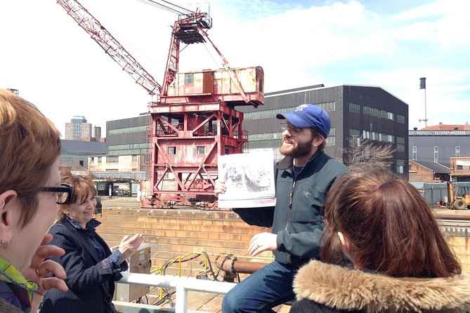A tour group enjoys a story told by one of the guides as he describes how dry docks work