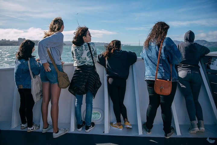 Travelers look at the view over the San Francisco Bay Area during the cruise to Alcatraz., photo
