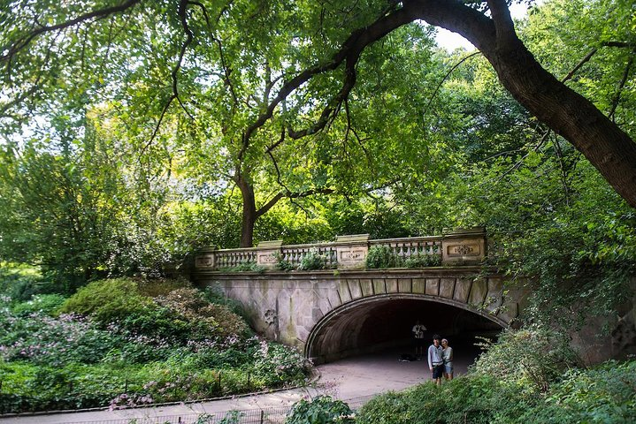 Pedestrians walk beneath the Glade Arch in Central Park.