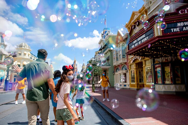 A family walk past Main Street Cinema in Magic Kingdom® Park, Walt Disney World®