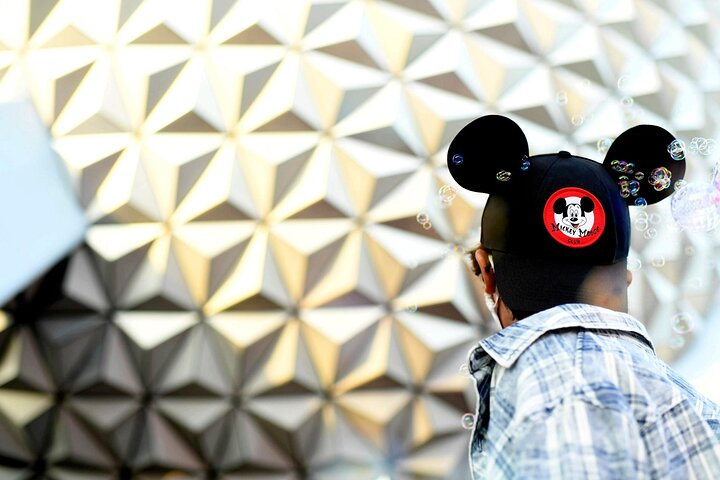 Visitor outside Epcot®'s Spaceship Earth wearing a Disney hat