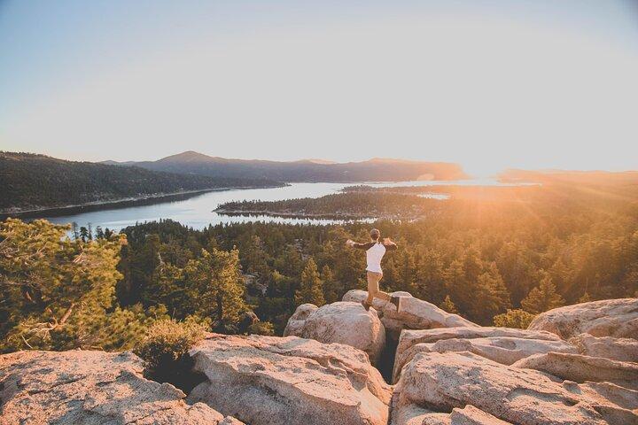 A traveler looks over Big Bear Lake at sunset