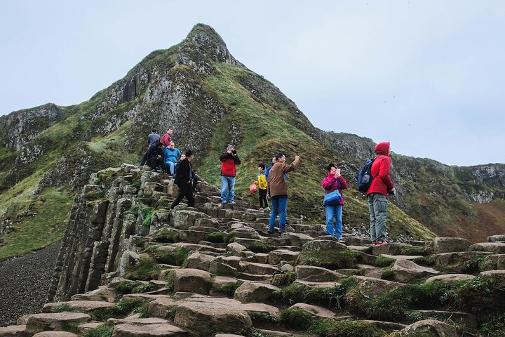 Travelers taking photos on the rock columns at Giant's Causeway, Northern Ireland
