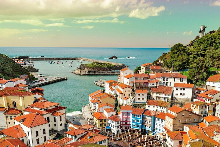 A cluster of terracotta roofs tumble down the Spanish coast in Cudillero, Spain.