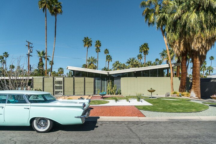 A turquoise car sits in front of a retro Palm Springs building surrounded by palm trees.