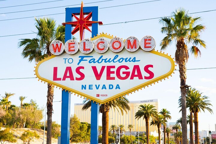 The Welcome to Las Vegas Sign with blue skies and palm trees in the background.