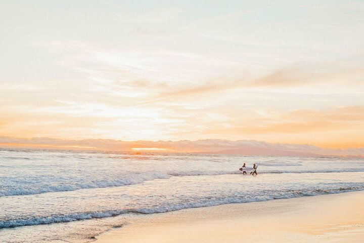 Two surfers stroll out to sea with their surfboards on Huntington Beach, California.