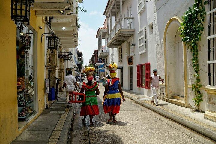Two women walk down a street in Cartagena, Colombia.