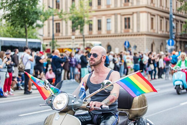 A bald-headed person rides down the street in Vienna, Austria on a rainbow-flagged motorbike.