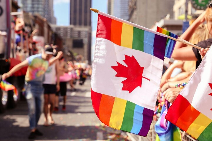 A person waves a rainbow-colored Canadian flag at Toronto Pride in Canada.