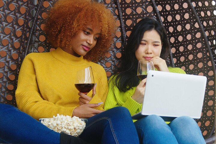 Two women watch a movie with wine and popcorn.