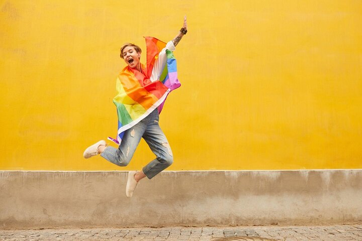 Young person jumps against a yellow background with a rainbow Pride flag.