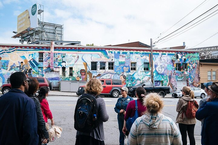 Tour guide and group stand by a notable mural in the Castro, San Francisco.