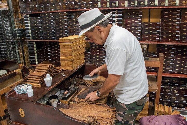 A man folds cigars in a Little Havana tobacco store.