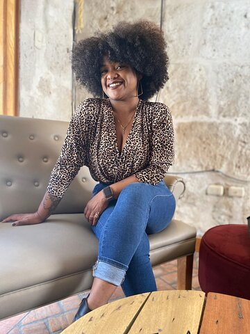 Josselyn Solano, a Black woman with afro hair smiles as the camera wearing a leopard print shirt and jeans.