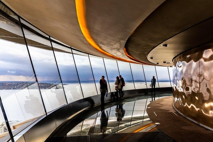 A group of travelers looking out over Seattle from the Space Needle observation deck