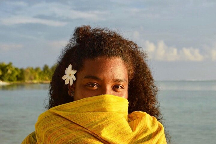 Adama looks at camera with loose afro hair and a yellow shawl over her face