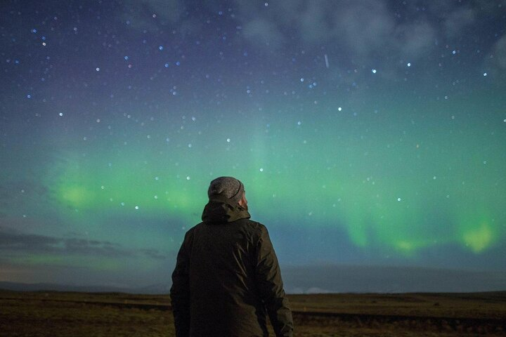 A man looks out over the northern lights in Iceland