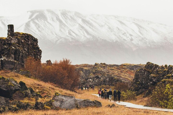 A group of tourists walk among the scenery during a Golden Circle tour, Iceland.