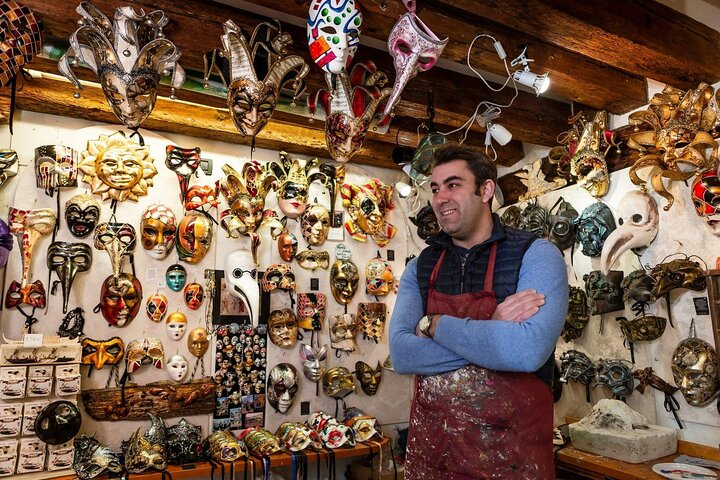 Man stands in front of a wall of Venetian carnival masks in Venice, Italy