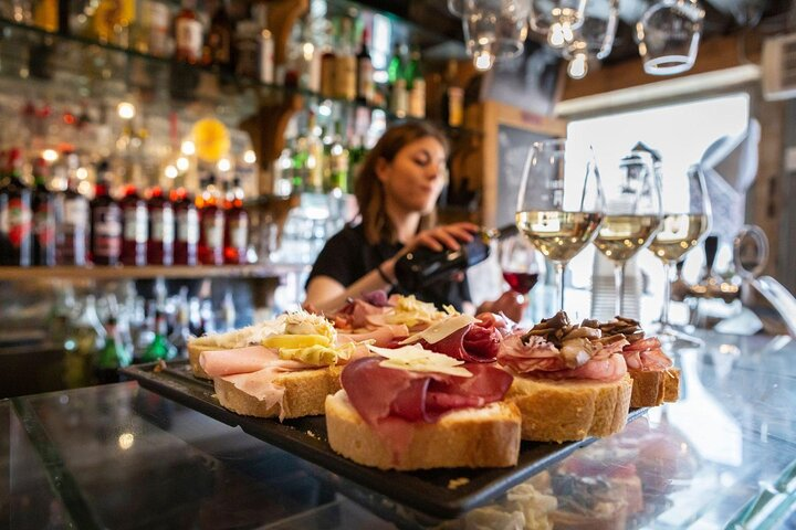 A woman pours wine with cicchetti on a plate in the foreground