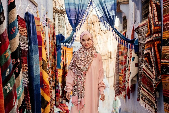 A woman stands in a street amid Moroccan rugs in Marrakech