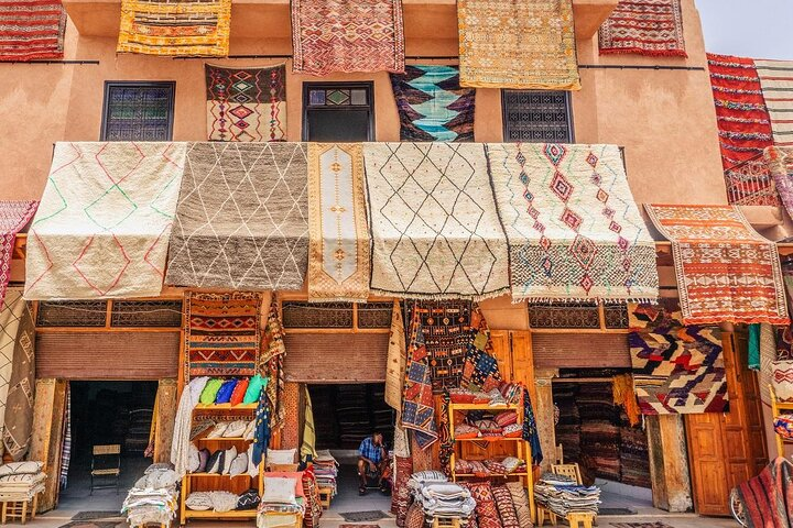 A merchant sits in the doorway of a carpet shop in Marrakech
