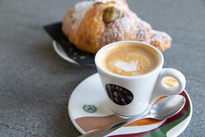 A typical Italian breakfast featuring a caffè macchiato and a cornetto