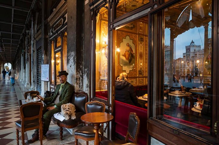 A well-dressed man sits outside the historic cafè Florian in San Marco Square, Venice, Italy
